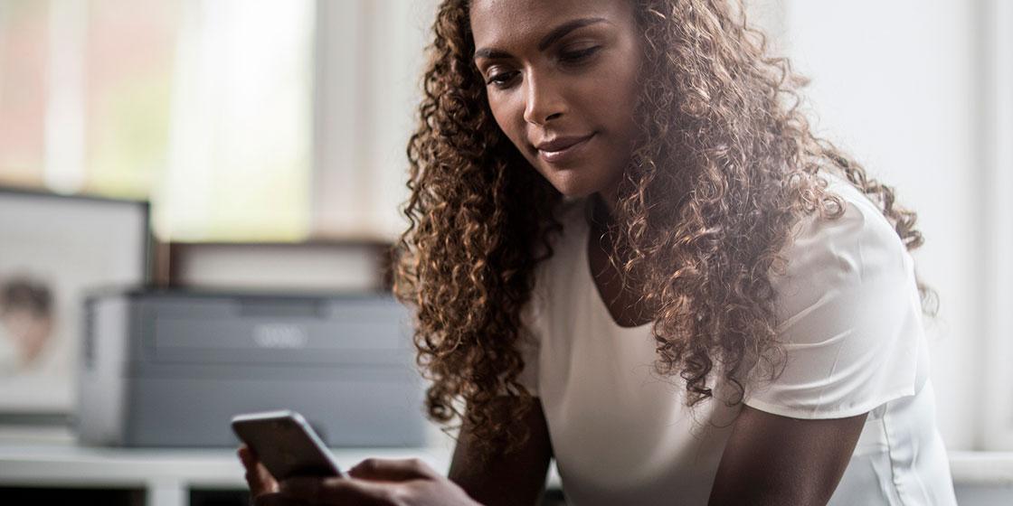 En kvinne ser på mobiltelefonen en Brother laserskriver står i bakgrunnen