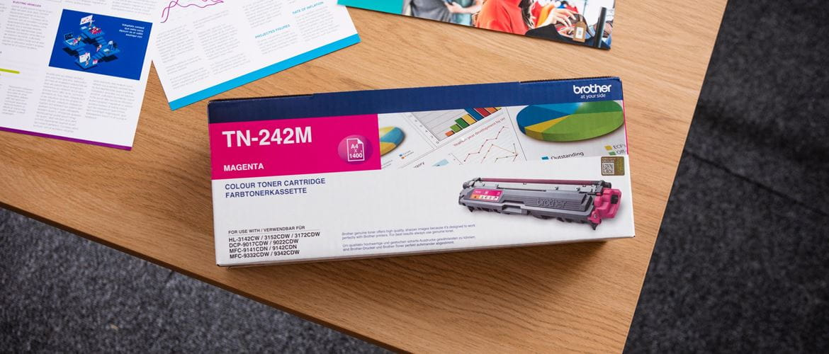 A top shot of a boxed Brother toner cartridge on a light brown office table against a dark grey carpet background