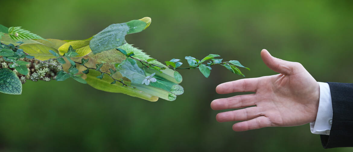 two hands shaking, one a man, one an environmental representation of a hand