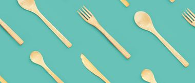 Environmentally friendly sustainable bamboo wooden cutlery (knife, fork and spoon) are lined up against a teal solid background