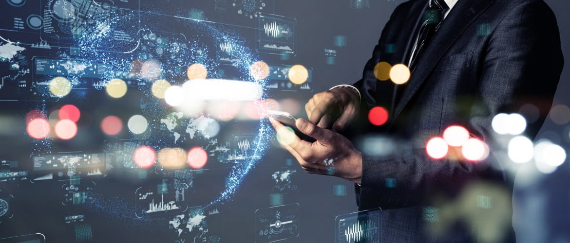 A futuristic image shows man in a business suit holding a smartphone while in the background there are futuristic light trails and examples of data being projected using holographic technology
