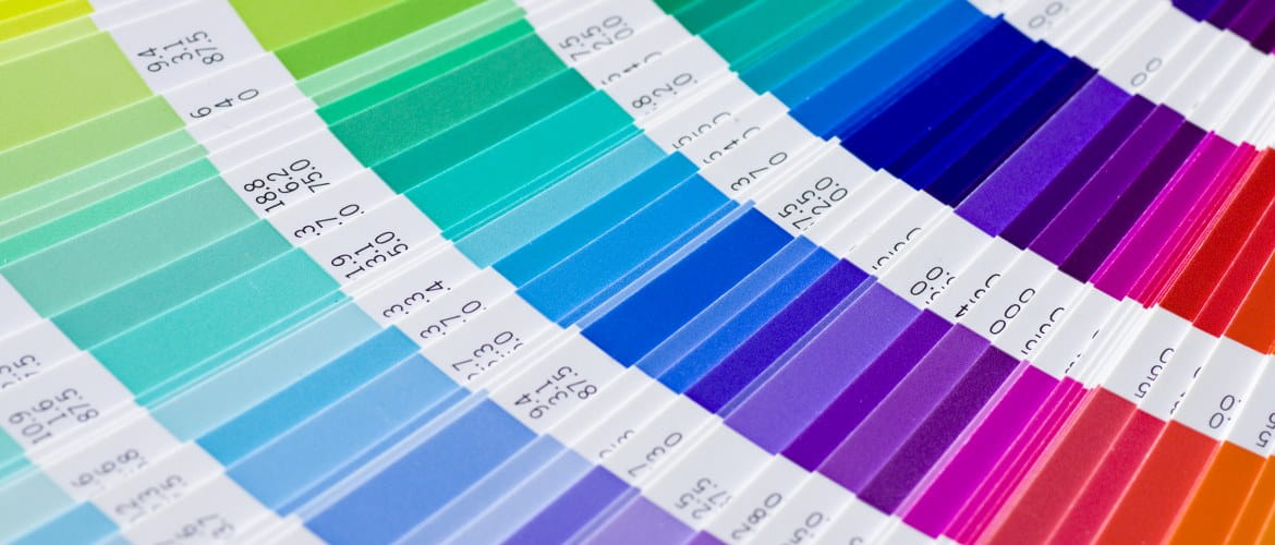 A selection of pantone colours is fanned out in a colour swatch formula guide chart