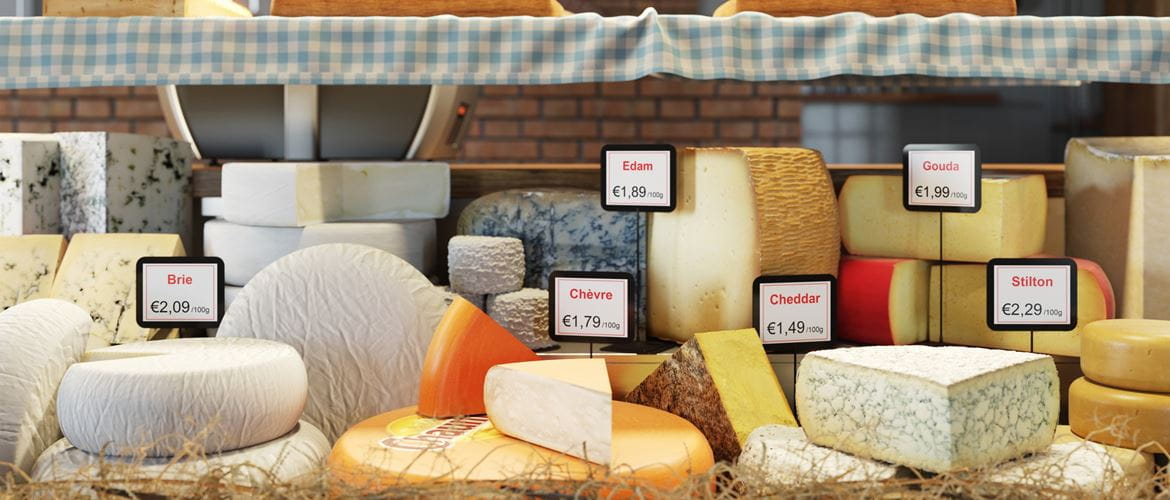 A selection of deli counter cheeses (Brie, chevre, Edam, cheddar, Gouda and Stilton) is on display in the fresh food shop complete with clearly marked Euro price labels and name tags for each cheese wedge