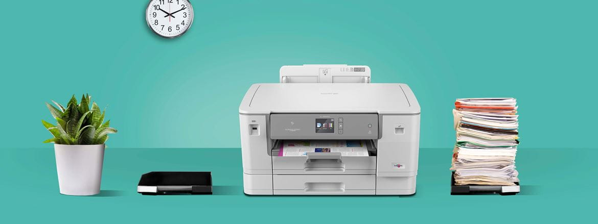 Brother xseries printer on table with stack of paperwork to right and plant on left