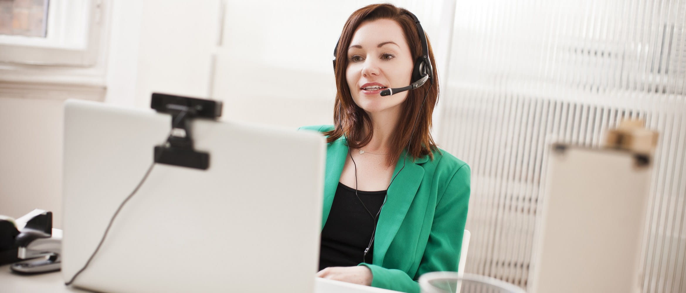 A woman wearing a microphone headset and a green business suit conducts a remote online video conferencing meeting in a home or small office environment.