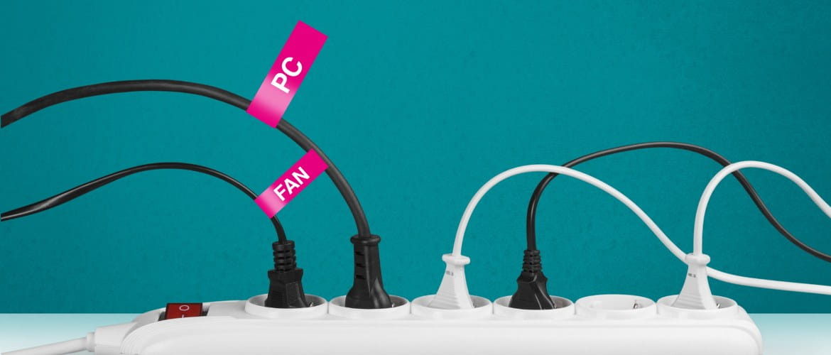 A multi-plug extension in the office has a variety of electrical devices plugged in. Only two of the five are brightly labelled with a bright pink label. They clearly identify a