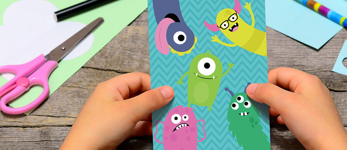 Child making a birthday card with monsters on from the creative center