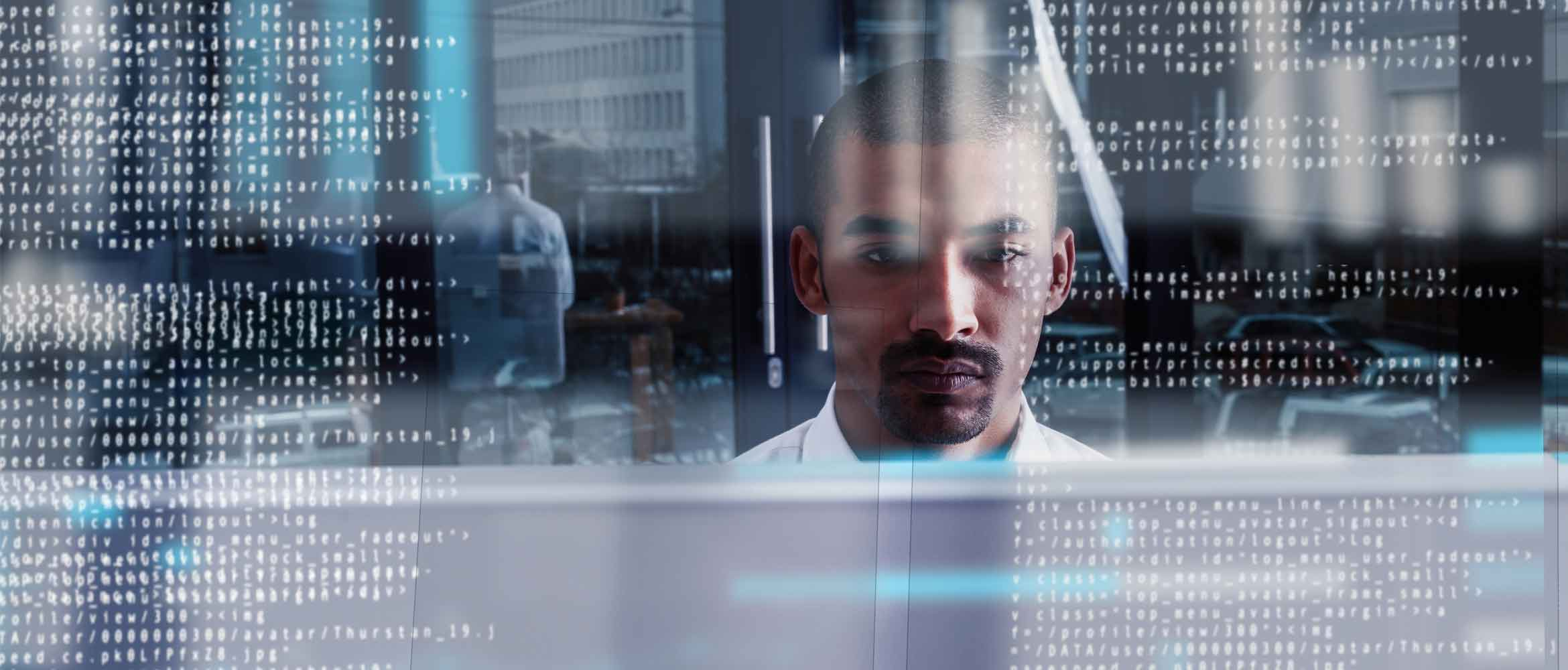 A man in a futuristic office scene is surrounded by numbers and code as he works from a computer screen