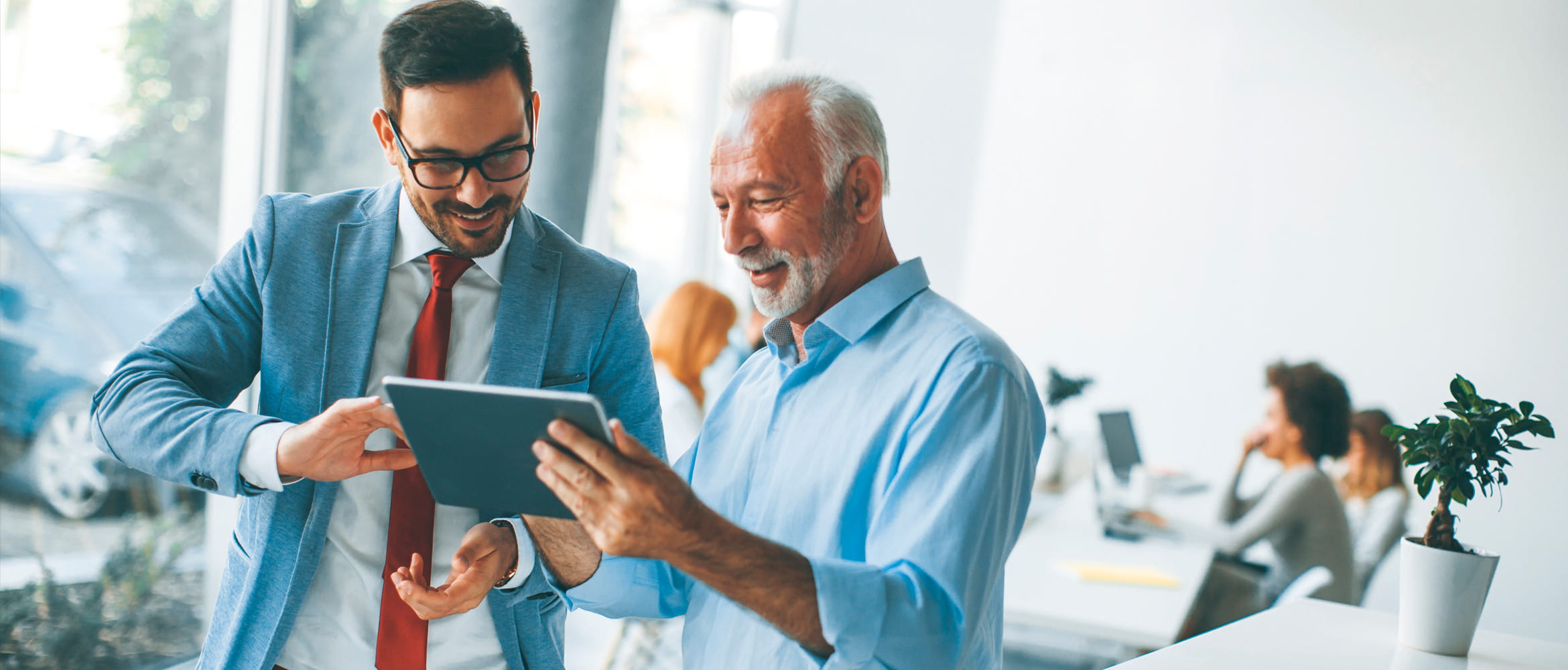 A young man in a bright suit and an older male co-worker in a more relaxed shirt discuss a business project on a tablet during a stand-up meeting in the more diverse and collaborative workplace of the future