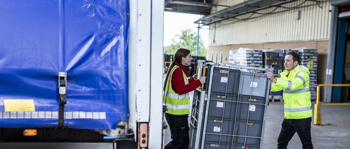 Direct store delivery, two warehouse workers in high visibility jackets moving grey crates onto the back of a lorry