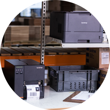 Dark grey Brother printer and label printer on bench, clipboard, paper, racking, boxes