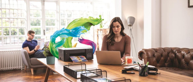 Imprimanta din care ies valuri viu colorate de cerneală în timp ce imprimă lângă un bărbat și o femeie care lucrează de acasă