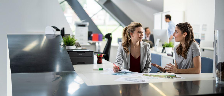 Dve ženski sedita v polni pisarni za mizo in se pogovarjata, moški v ozadju, tiskalniki, pisala, dokumenti