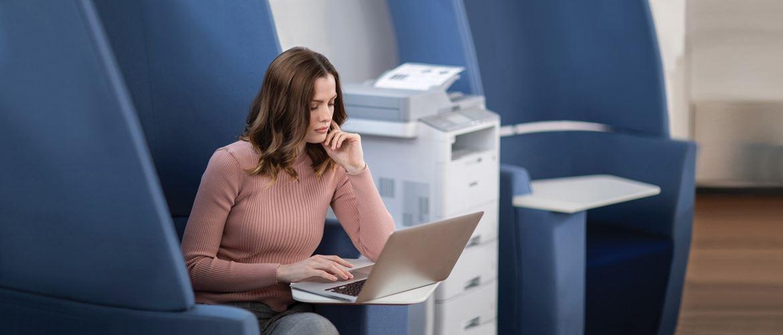 Ženska sedi v modrem naslonjaču poleg večfunkcijske naprave MFC-L6900DW v pisarni