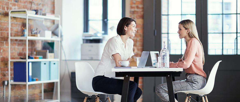 Dve ženski imata sestanek v pisarni, sedita za mizo, opečnata stena