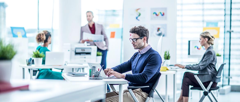 Dva muži a dvě ženy sedí v kanceláři s inkoustovou tiskárnou Brother v pozadí