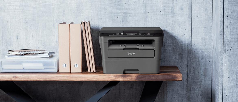 Črno-bel laserski tiskalnik Brother na polici, siva stena