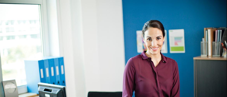 Ženska v pisarni z različnimi pisarniškimi predmeti, označenimi okoli nje