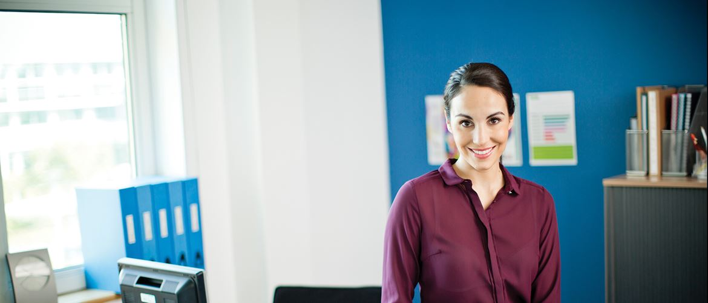 Hölgy egy irodában, különféle irodai eszközökkel, feliratokkal ellátva