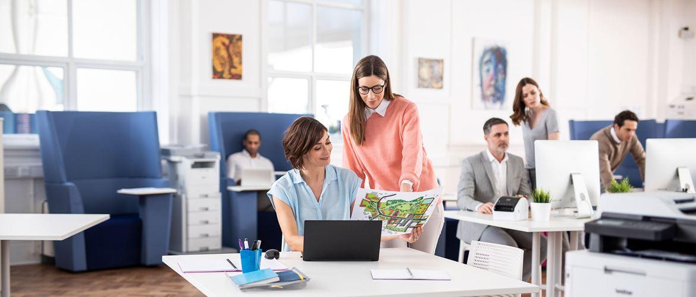 dużo ludzi pracuje w biurze na laptopach, rozmawiają ze sobą