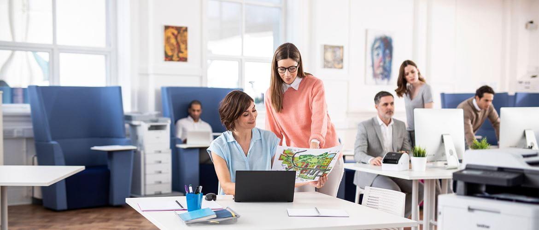 Mozgalmas irodai életkép, a kollégák laptopon dolgoznak