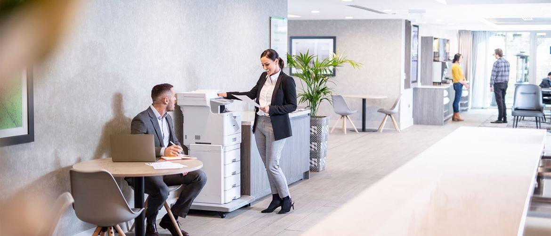Žena u jakni stoji kod laserskog višenamjenskog uređaja Brother MFC-L9570CDWTT, muškarac u jakni sjedi za stolom s prijenosnim računalom, ljudi u pozadini
