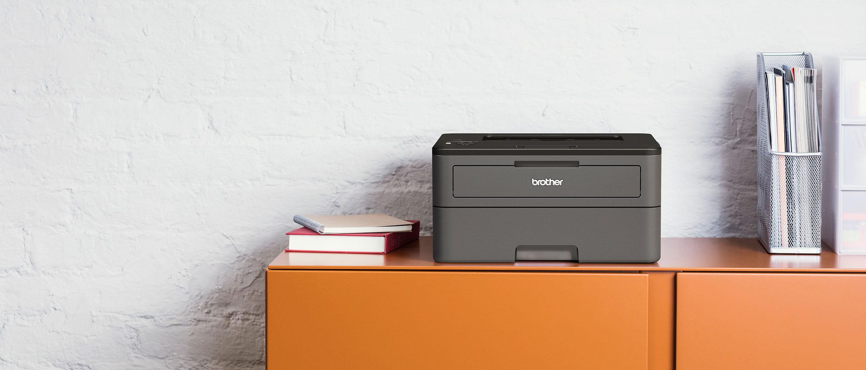 Tiskárna Brother HL-L2375DW na oranžové skříni, knihy, drátěný stojan na dokumenty, papír
