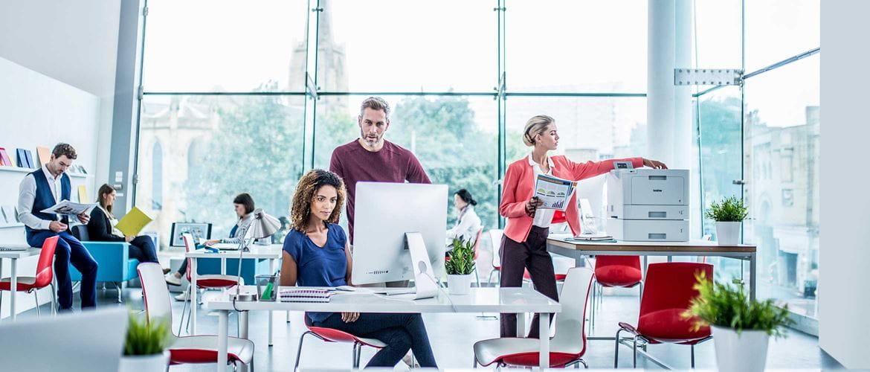 Polna pisarna z žensko, ki sedi za pisalno mizo, poleg nje stoji moški, desno ženska, ki stoji poleg laserskega tiskalnika Brother HL-L9310CDW na pisalni mizi.