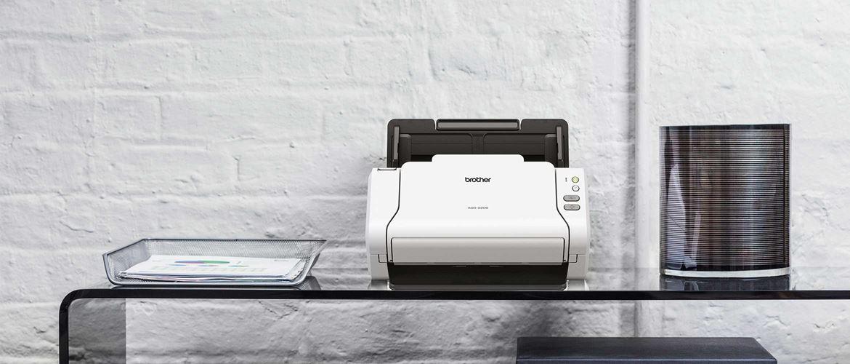 skaner stacjonarny Brother ADS-2200 stoi na szklanym stole, druciany pojemnik na papier