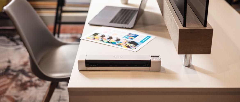 przenośny skaner dokumentów DSmobile DS-940DW leży na biurku, kolorowy dokument A4, laptop, szare krzesło
