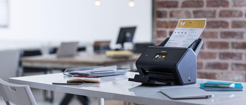 skaner ADS-3600W stoi w biurze, w podajniku widoczna kartka