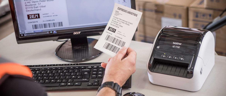 stacjonarna drukarka etykiet Brother QL-1100 stoi na biurku, osoba siedząca przy biurku trzyma w ręku etykietę
