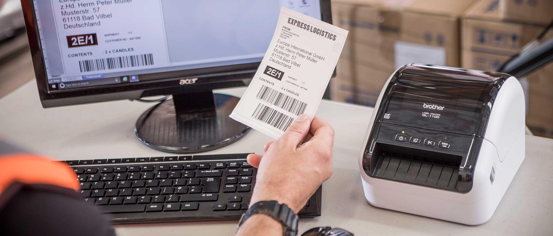 Brother QL-1100 настолен етикетен принтер на бюро. Служител, седнал на бюрото, държи етикет