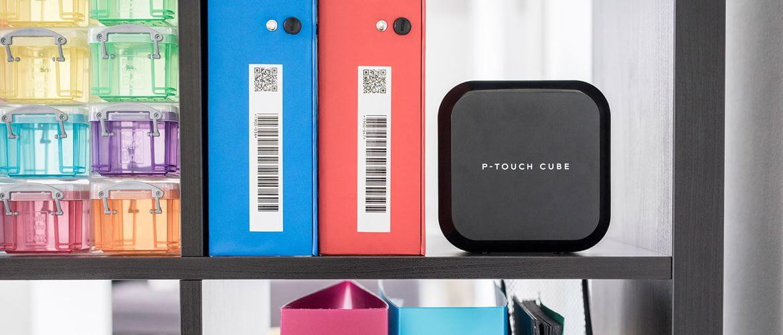 Tiskalnik nalepk Brother P-touch Cube na polici poleg označenih fasciklov s črtnimi kodami