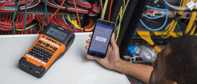Hálózati technikus, aki okostelefont tart a kezében és az ingyenes Brother iLink & Label alkalmazást használja a kábelazonosítók átvitelére a Brother PT-E550WNIVP címkenyomtatóra