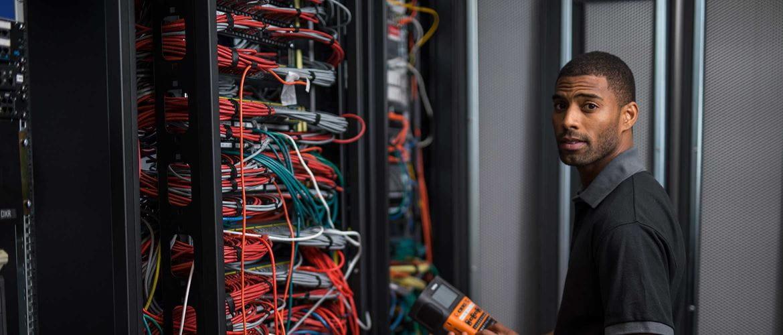 Instalator trzyma w ręku drukarkę etykiet stojąc przed szafą z kablami