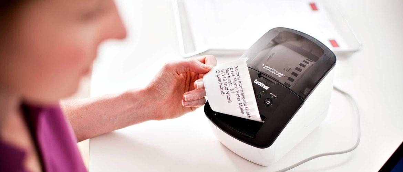 kobieta wyjmuje wydrukowaną naklejkę z drukarki etykiet Brother QL