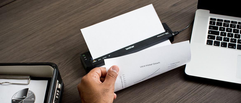 Brother PJ dokumentni tiskalnik na rjavi mizi poleg prenosnika