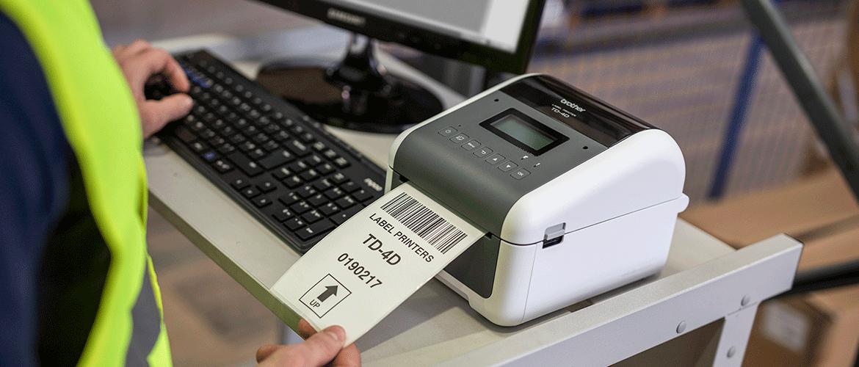 Muž bere štítek z tiskárny Brother TD-4D umístěné na stole s monitorem počítače a klávesnicí