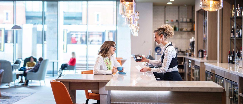 Konobarica poslužuje ženu za šankom; boce, svjetla, stolice i šalice