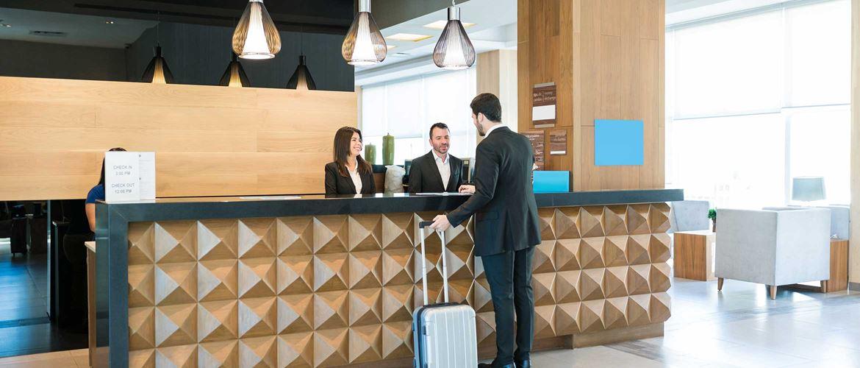 Receptor in receptorka v hotelu se pogovarjata s stranko, ki ima kovček; mize, stoli