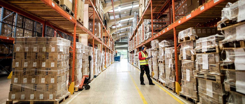 Radnica u skladištu i distribucijskom centru u signalnom prsluku, drži mapu, kutije, narančaste police