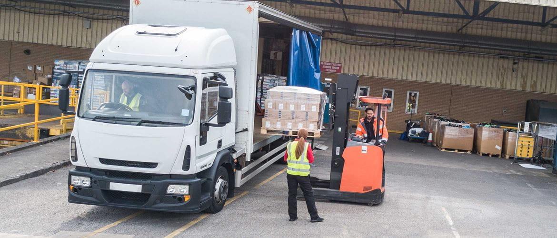Moški sedi v tovornjaku in tiska, moški z viličarjem daje paleto na tovornjak, ženska v opozorilnem jopiču