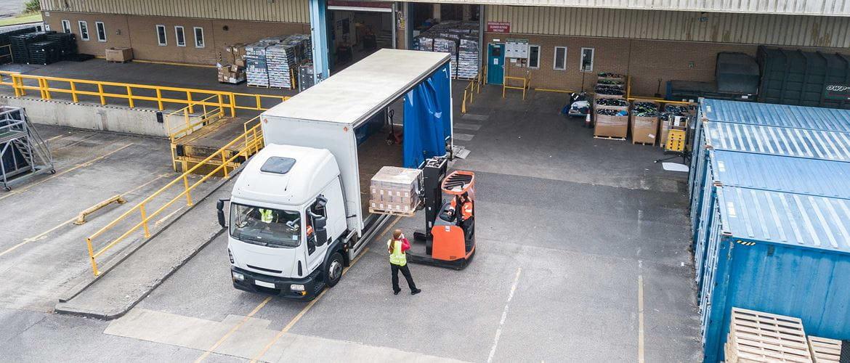 Transport in logistika, pogled iz zraka na nakladalnik, belo-modri kombi, oranžni viličar, oseba v opozorilnem jopiču