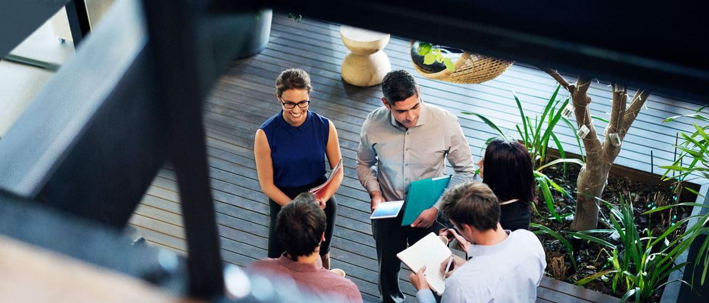 Pieciu pracowników w miejscu pracy przyszłości odbywa spotkanie biznesowe na korytarzu. Scena jest przedstawiona z góry. Zespół trzyma pliki, notesy i tablety w trakcie rozmowy.