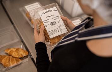 Žena s modrobílou pruhovanou zástěrou drží pekárenské výrobky se štítkem na plastové krabičce