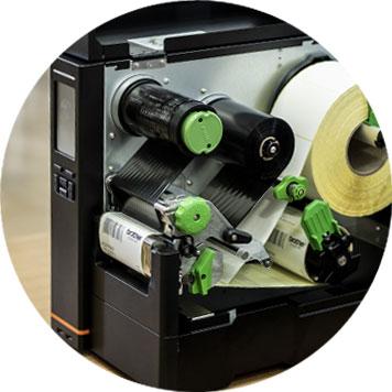 Odprt tiskalnik, bela rola nalepk, zelen mehanizem, valjčki