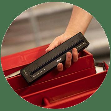 Oseba drži kompaktni tiskalnik Brother PJ-7 pred rdečo kovinsko škatlo