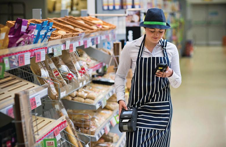 Asystentka sklepu idzie w supermarkecie z drukarką etykiet RJ przy biodrze