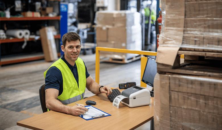 Moški z opozorilnim jopičem dela za mizo s tiskalnikom nalepk TD4D Brother v skladišču